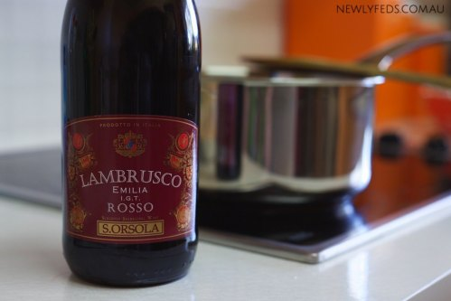 A photo of a bottle of Lambrusco next to a pot on the stove